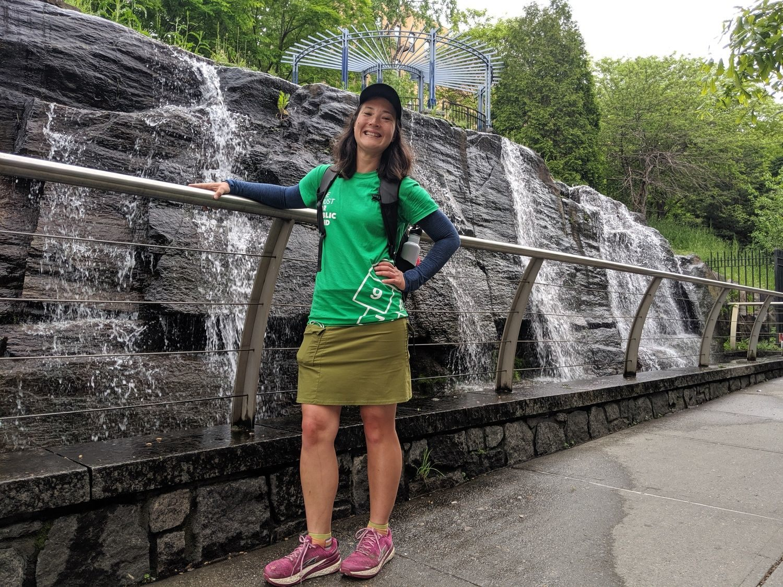 Liz Thomas wearing the Lululemon Swiftly Tech long sleeve shirt standing next to a waterfall in New York City.