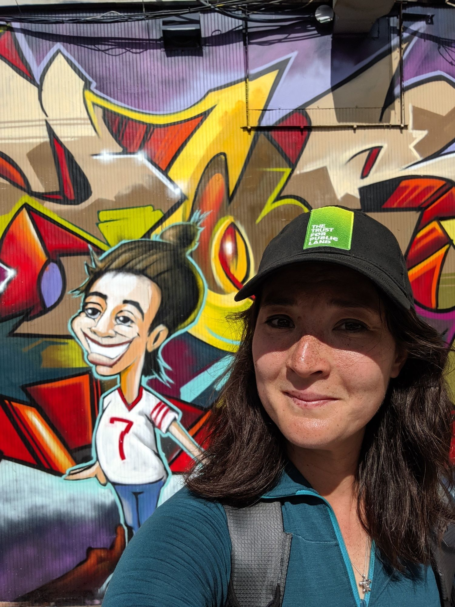 Liz Thomas wearing the Arc'Teryx Zip Satoro shirt standing in front of a graffiti wall in New York City.