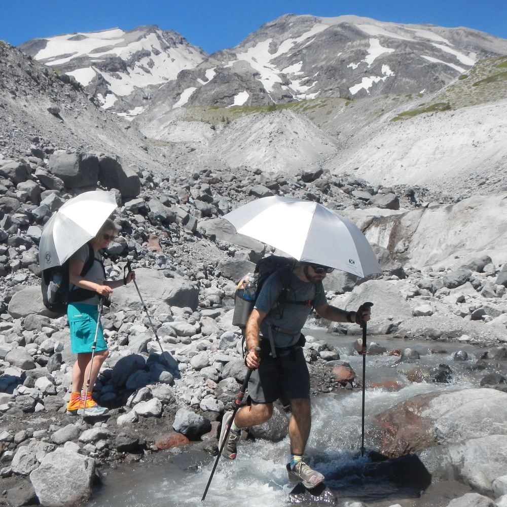 Two hikers crossing a stream with sun umbrellas.