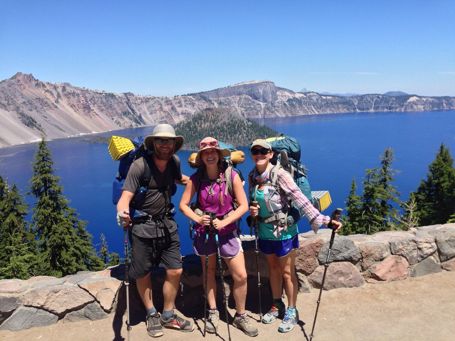 Three hikers at Crater Lake National Park, all using trekking poles.