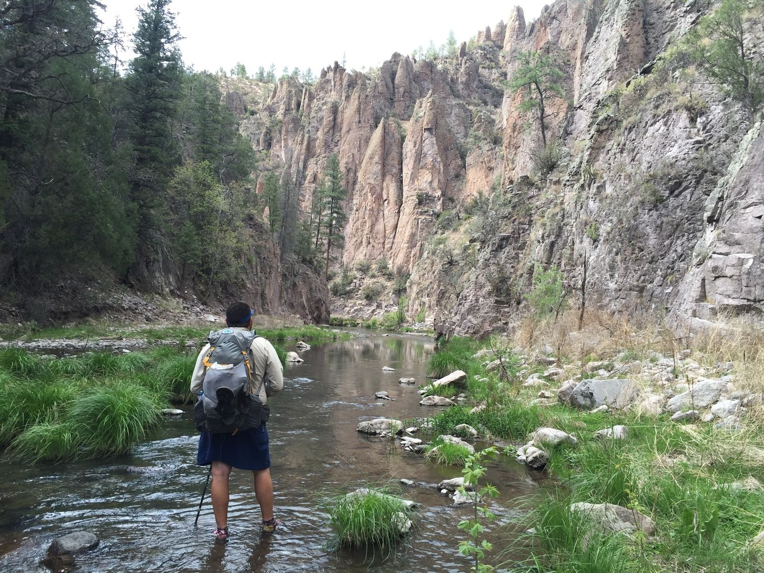 A hiker with trekking poles crossing a stream in a canyon.
