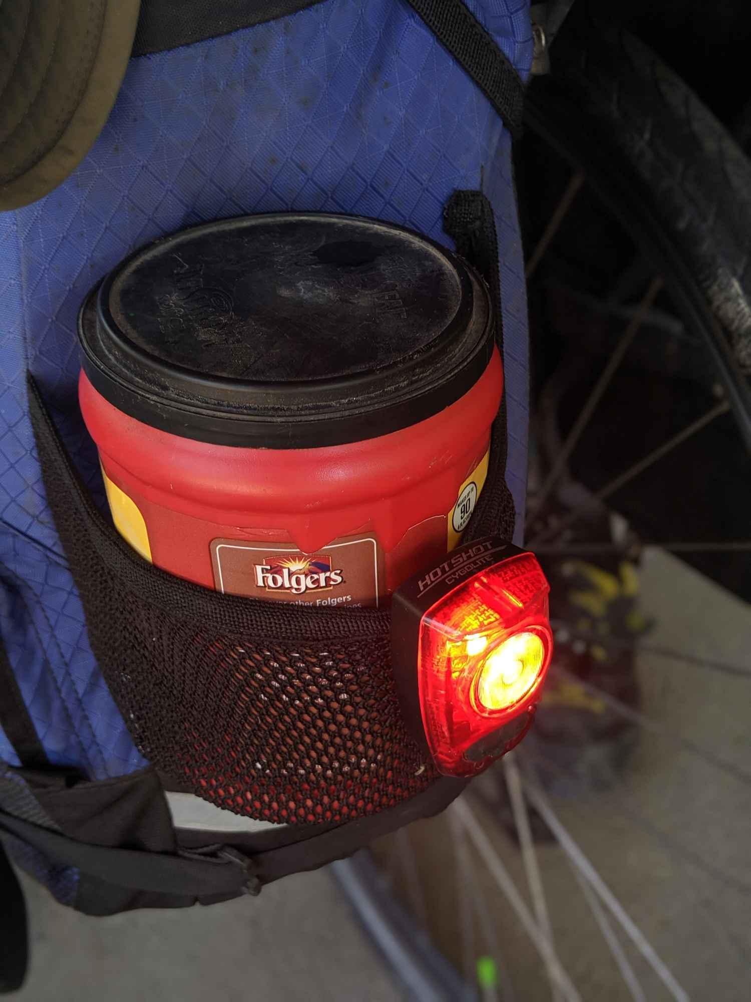 Brandon mounts his rear red light near his coffee can.   Photo by Liz Thomas.
