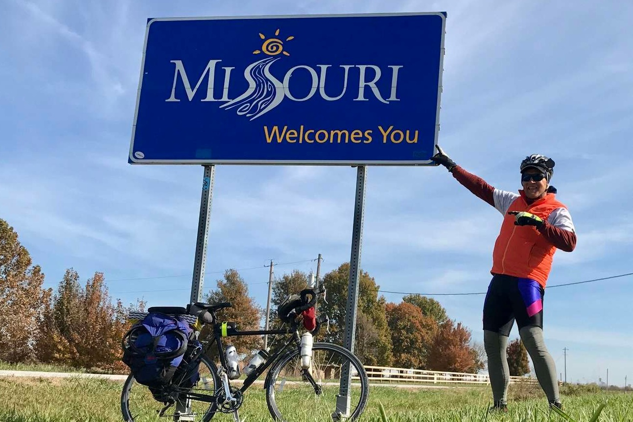 Brandon with his fully-loaded bike touring system at the Missouri border.   Photo courtesy Brandon Lampley.