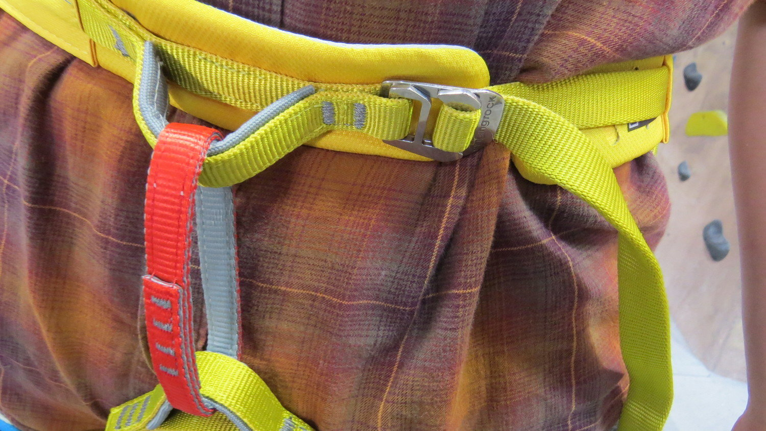 The bright yellow waist belt and red belay loop of the Singing Rock Onyx.   Photo by Liz Thomas.