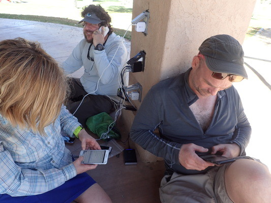 Hikers charging phones at Christmas Circle Park, Borrego Springs, California. Surrounded by Anza Borrego Desert State Park, this is a rare break in civilization for cyclists and hikers on the Trans San Diego County Route. Both cyclists and hikers recharge their phones at the outlets at Christmas Circle Park.   Photo by Liz Thomas