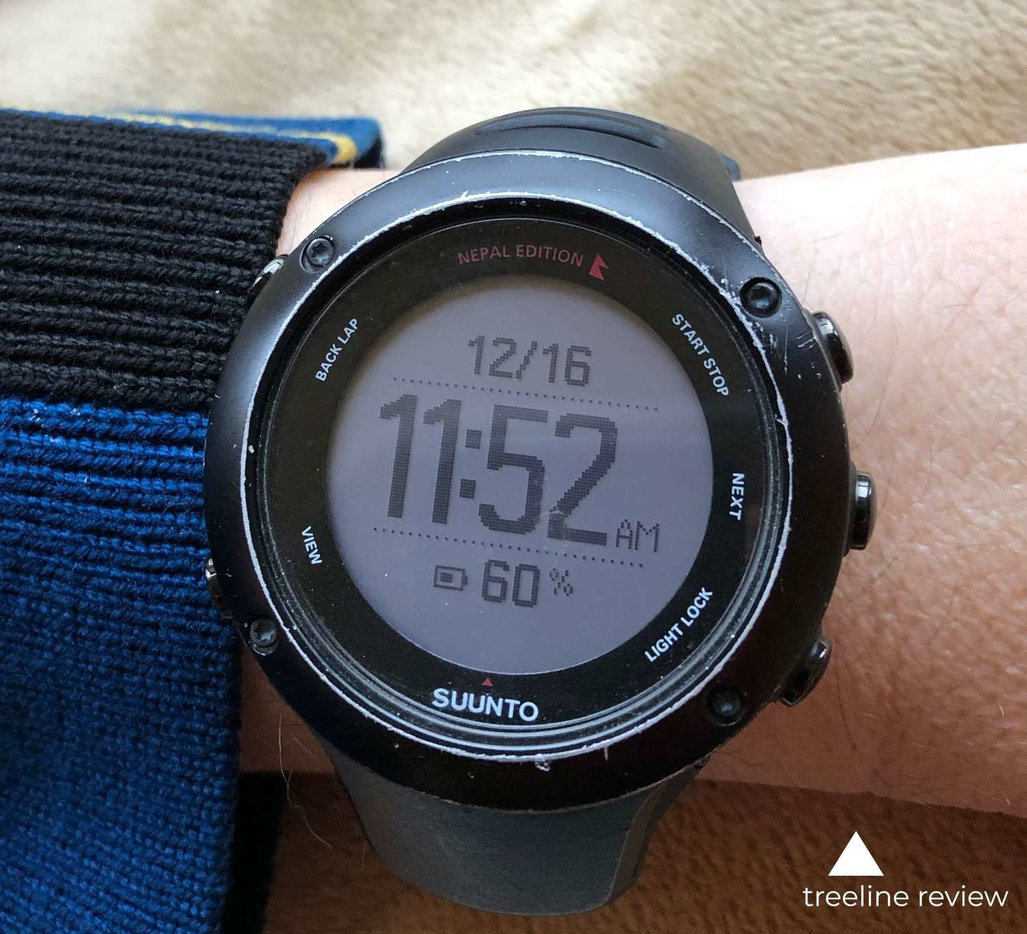 A close up view of the Suunto Ambit3 displaying time, date, and battery life data.