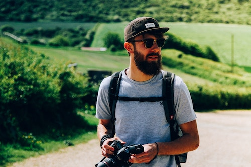 A man wearing a travel backpack with a camera.
