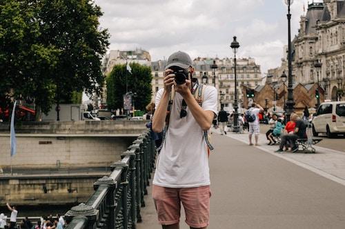 Man taking a photo in a European scene.