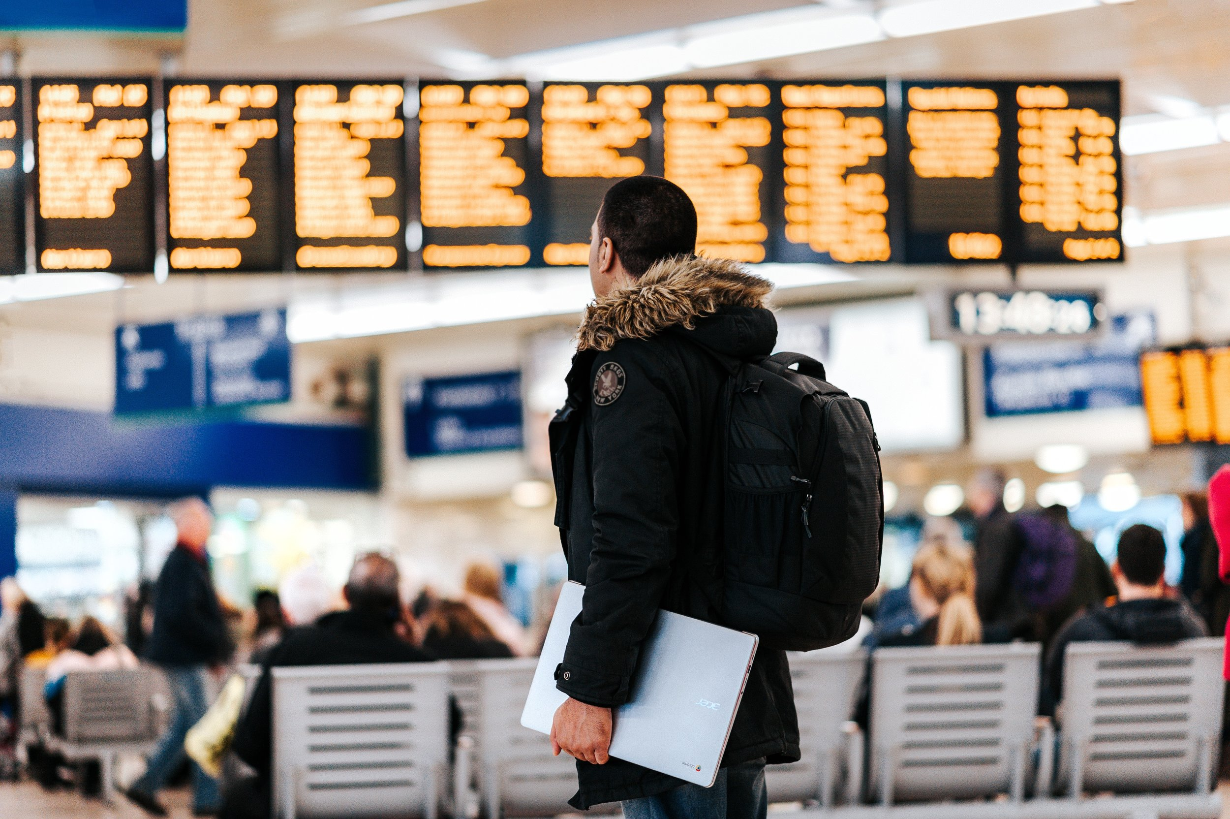 Man wearing a travel backpack in an airport.