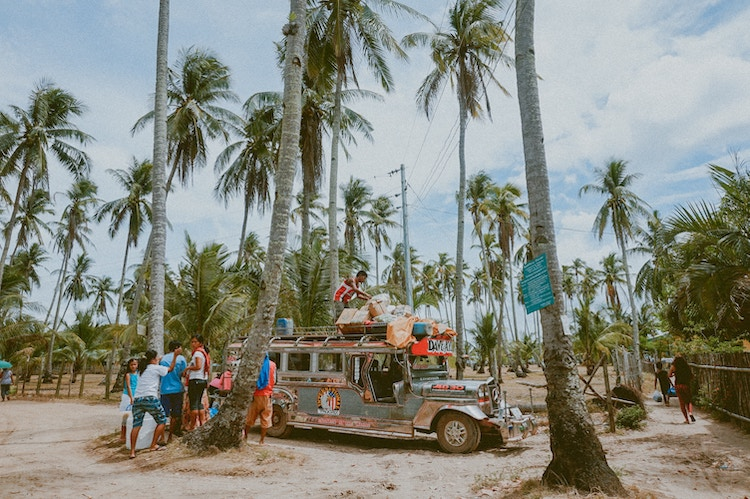 Travel bus loaded with travel backpacks in a tropical scene.