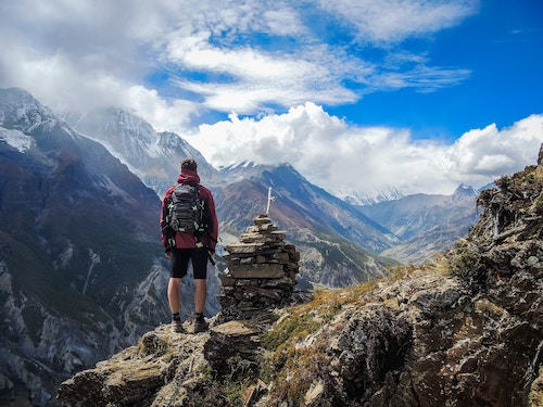Person standing in an alpine mountain scene wearing a backpack.