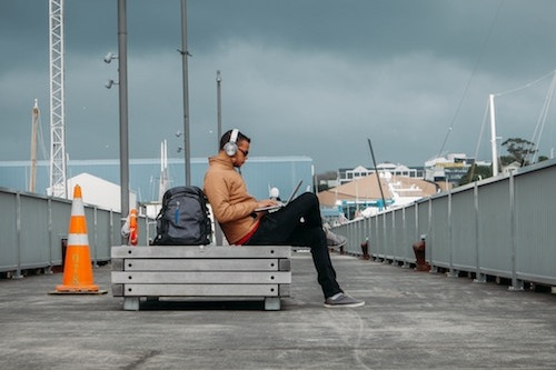 Man sitting on a bench with his travel backpack.