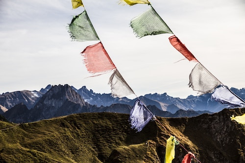 Prayer flags with mountains in the background.