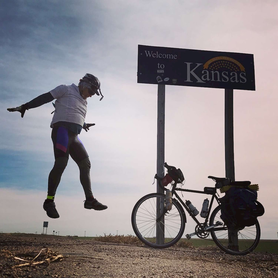 A road cyclist in a helmet at the Kansas State Line.   Photo by Brandon Lampley