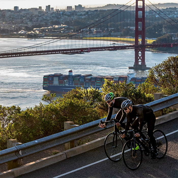 Two bicyclists wearing the Bell Stratus MIPS with the Golden Gate Bridge in the background.