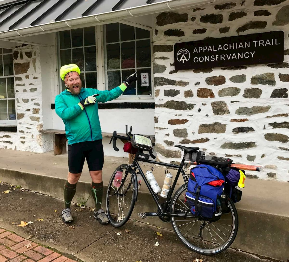 A bikepacker celebrates after reaching the Appalachian Trail Conservancy in Harpers Ferry, WV.