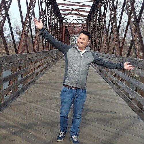 Kevin Tatsugawa standing on a bridge.
