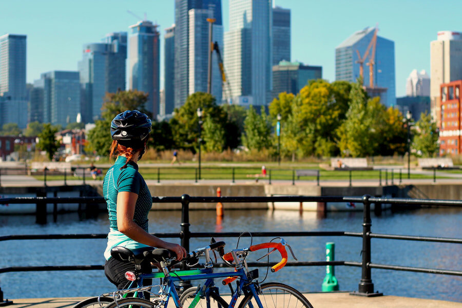 A woman standing next to her bike overlooking a city.