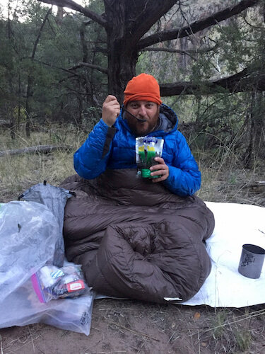 Camper enjoying a freeze dried meal with a long handled spoon