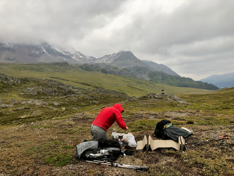 Hiker in Canadian Rockies with gear spread out