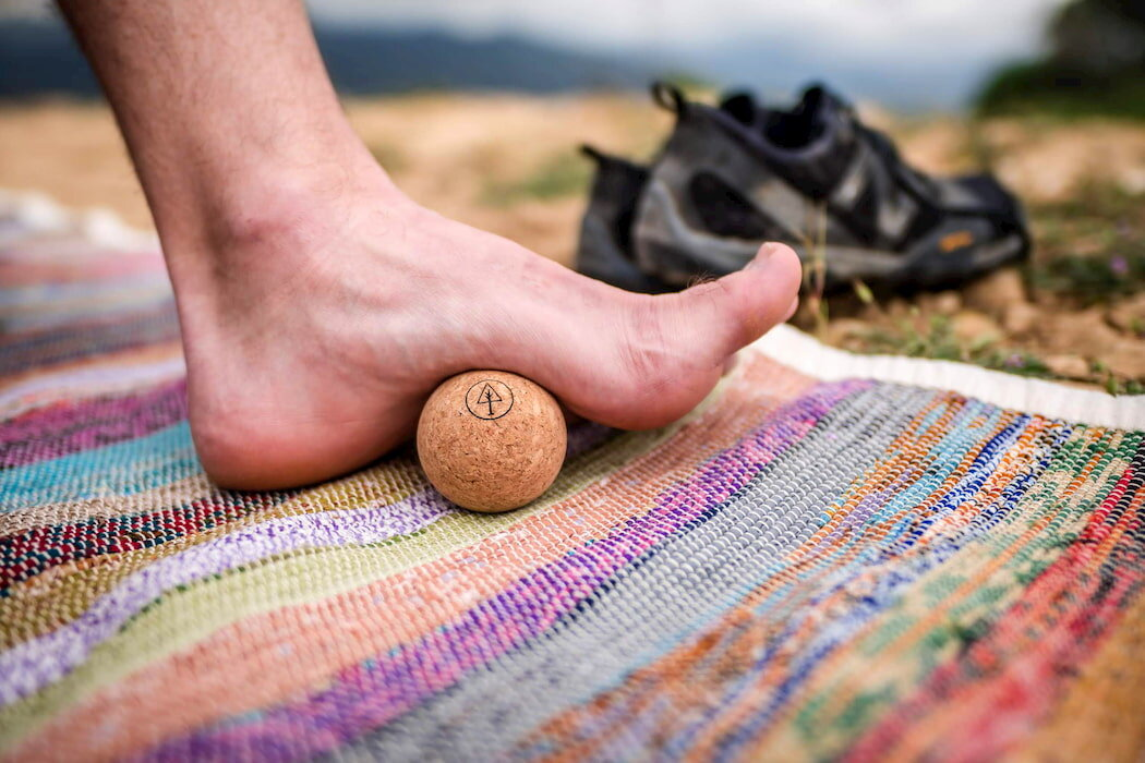The Rawlogy cork massage ball being used on a foot.