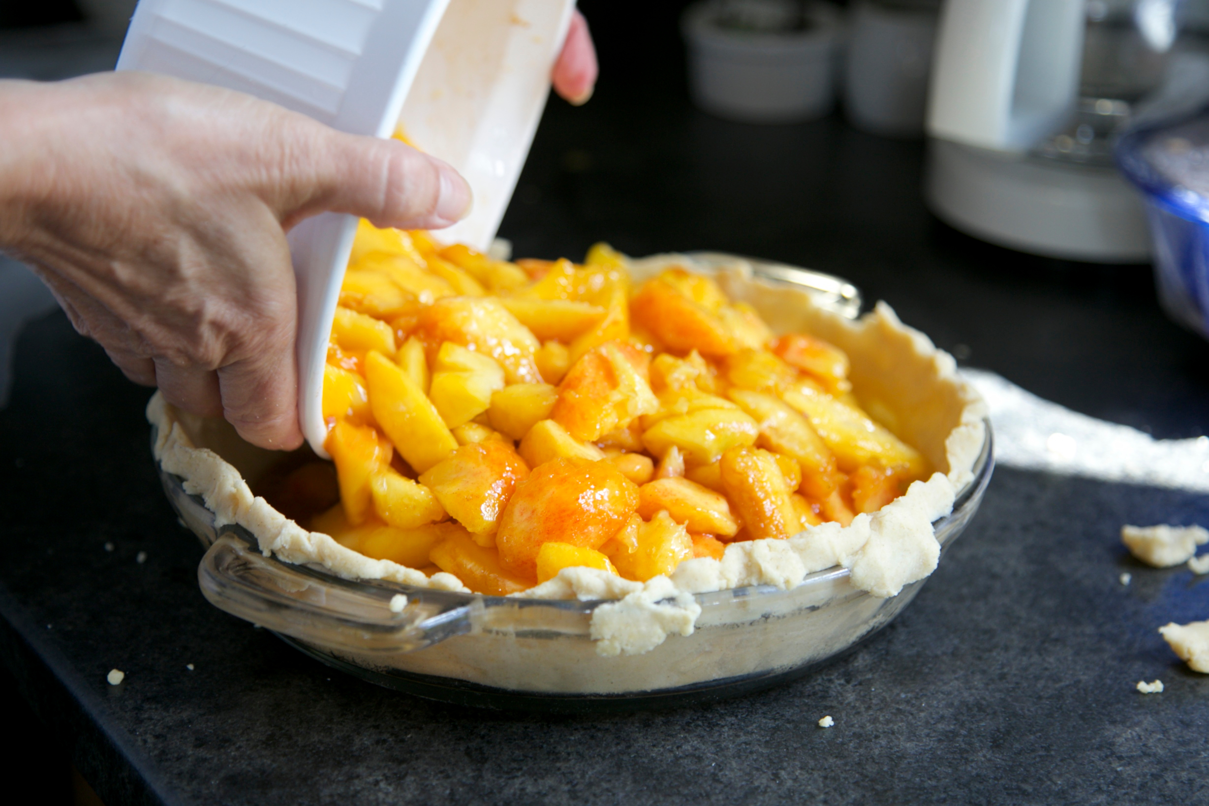 Canva - Person Pouring Cooked Food from Ramekin to Pie Tray on Gray Surface.jpg