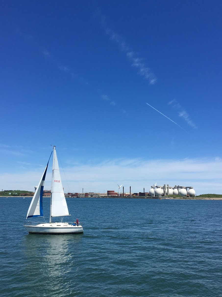 Scenic view of a sailboat and the wastewater treatment plant