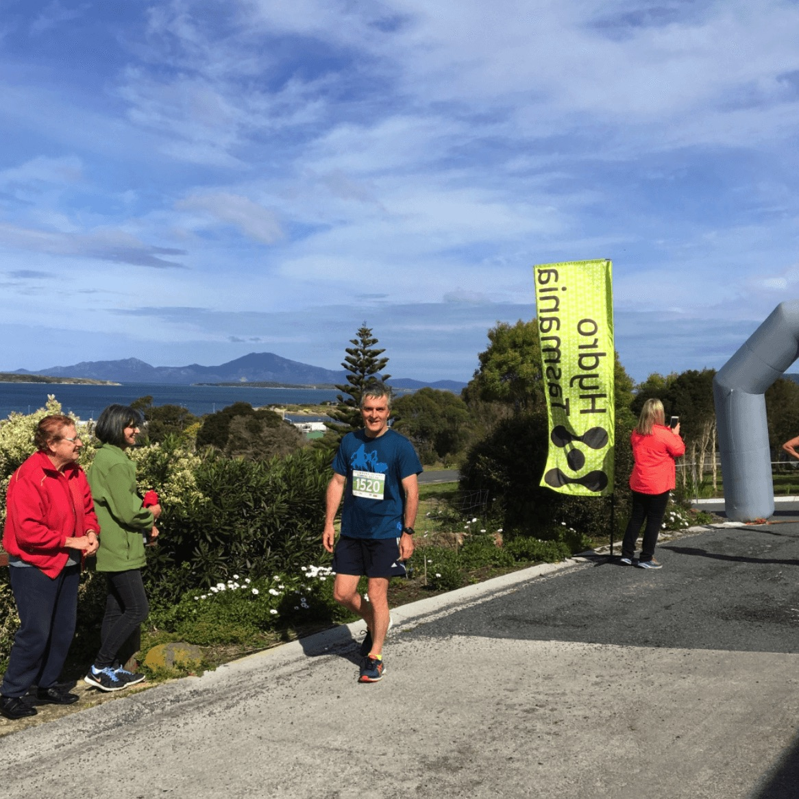 Fig 3 David Heap, an original committee member of the Running Festival and local physiotherapist, after crossing the finish line of the 2017 Pub to Pub outside Lady Barron's Furneaux Tavern.
