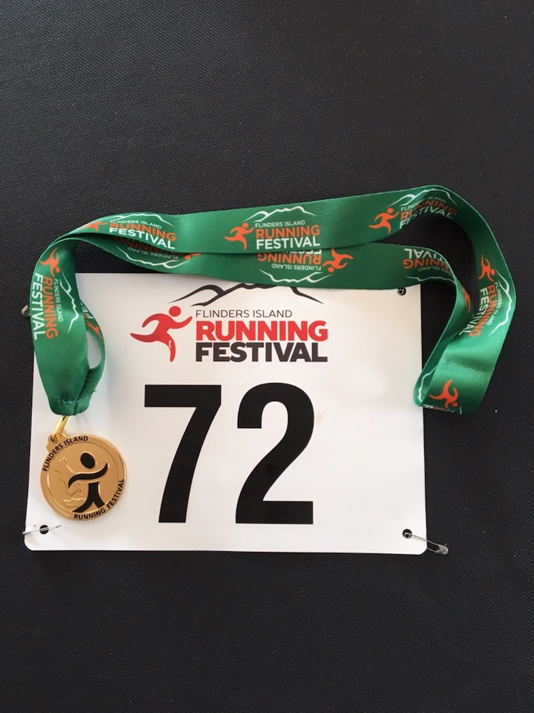 Participant's bib and finish medallion on a lariat.