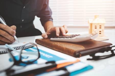 93009739-business-man-accountant-using-calculator-to-calculating-bugget-money-tax-loan-.jpg