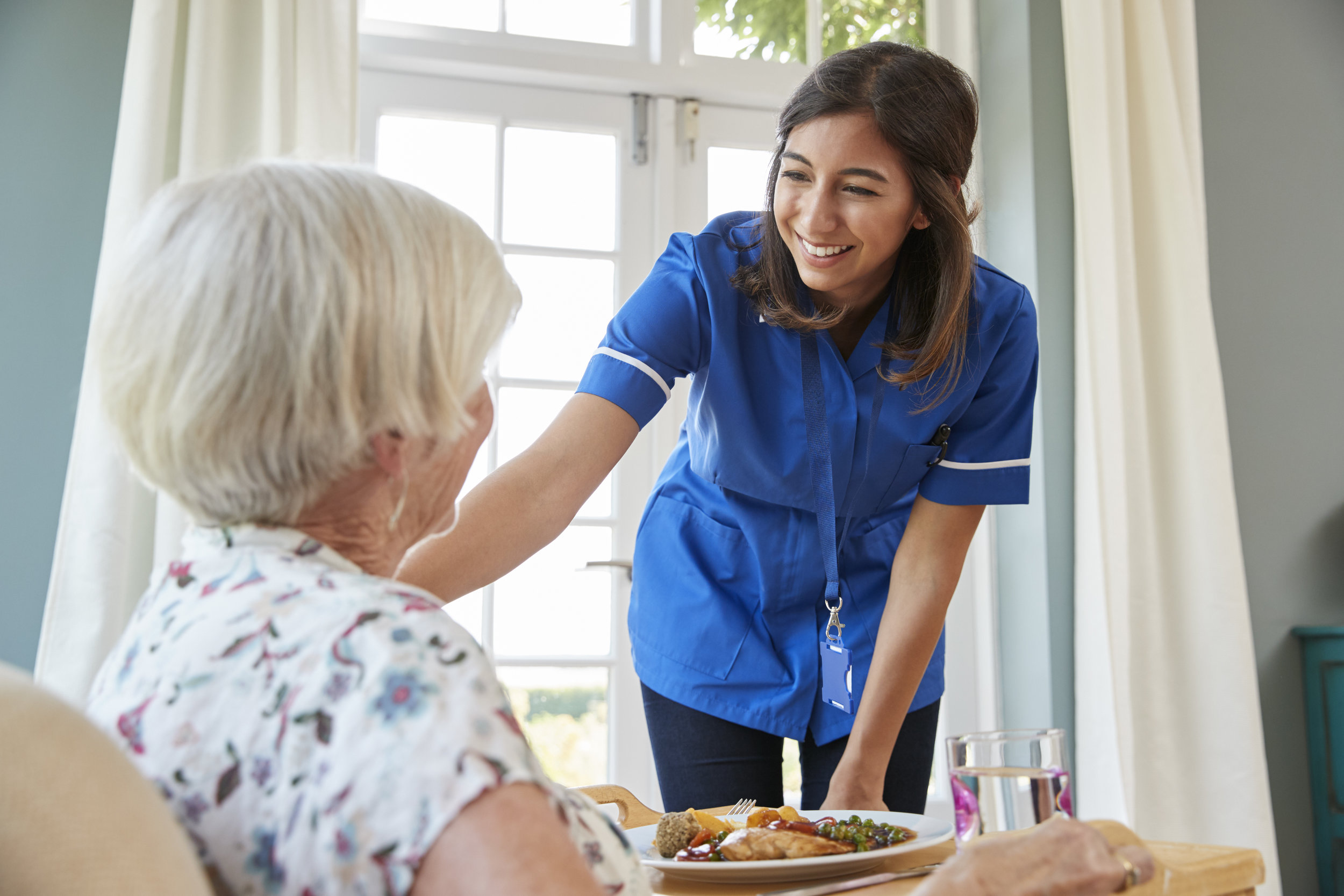 care-nurse-serving-dinner-to-a-senior-woman-at-PQHJS4A.jpg