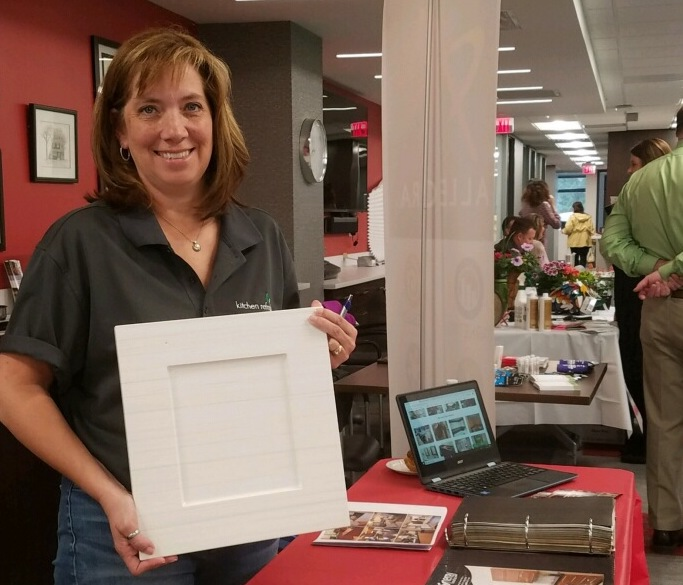 Shelly Carr, representing Kitchen Refresh, holds a sample door at the Edina Realty Vendor Fair.