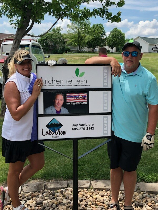 Kitchen Refresh franchisees Jennifer and Chuck Limoges by their hole sponsor sign.