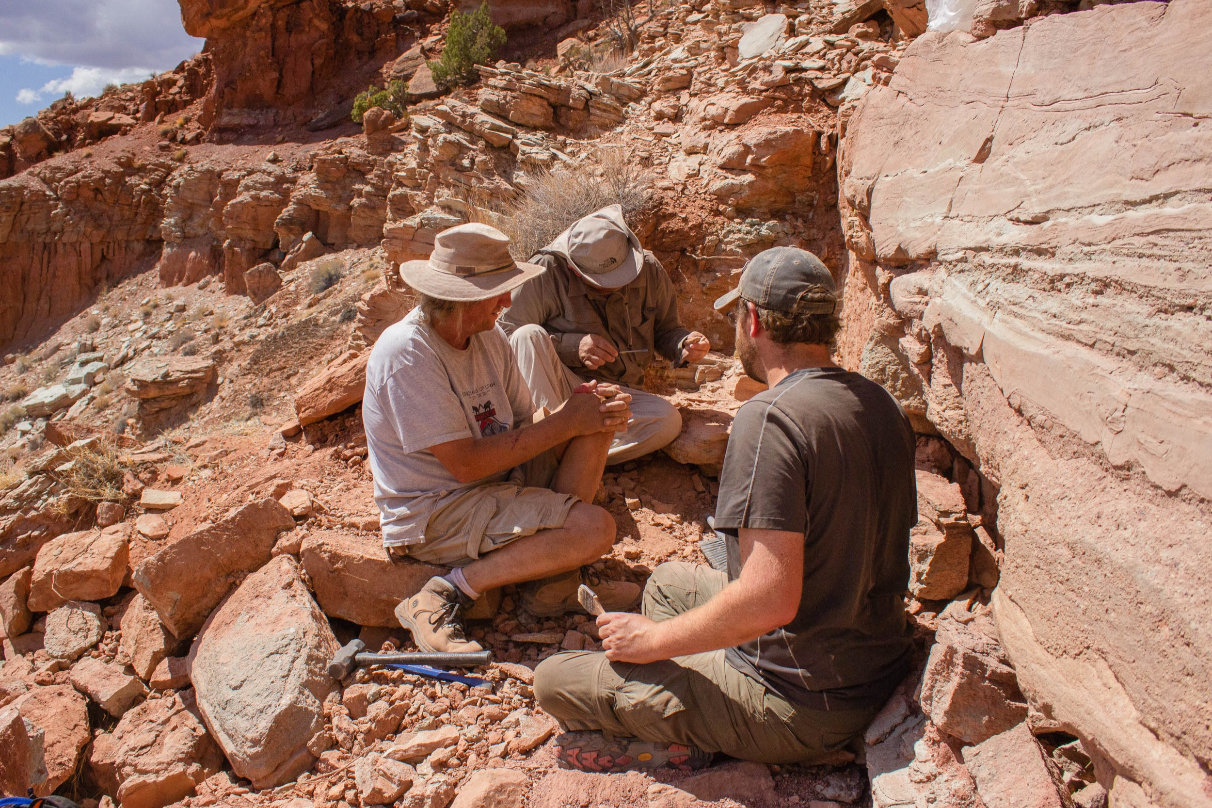 three men huddle around a piece of rock with hand tools, excavating a fossil out in the desert