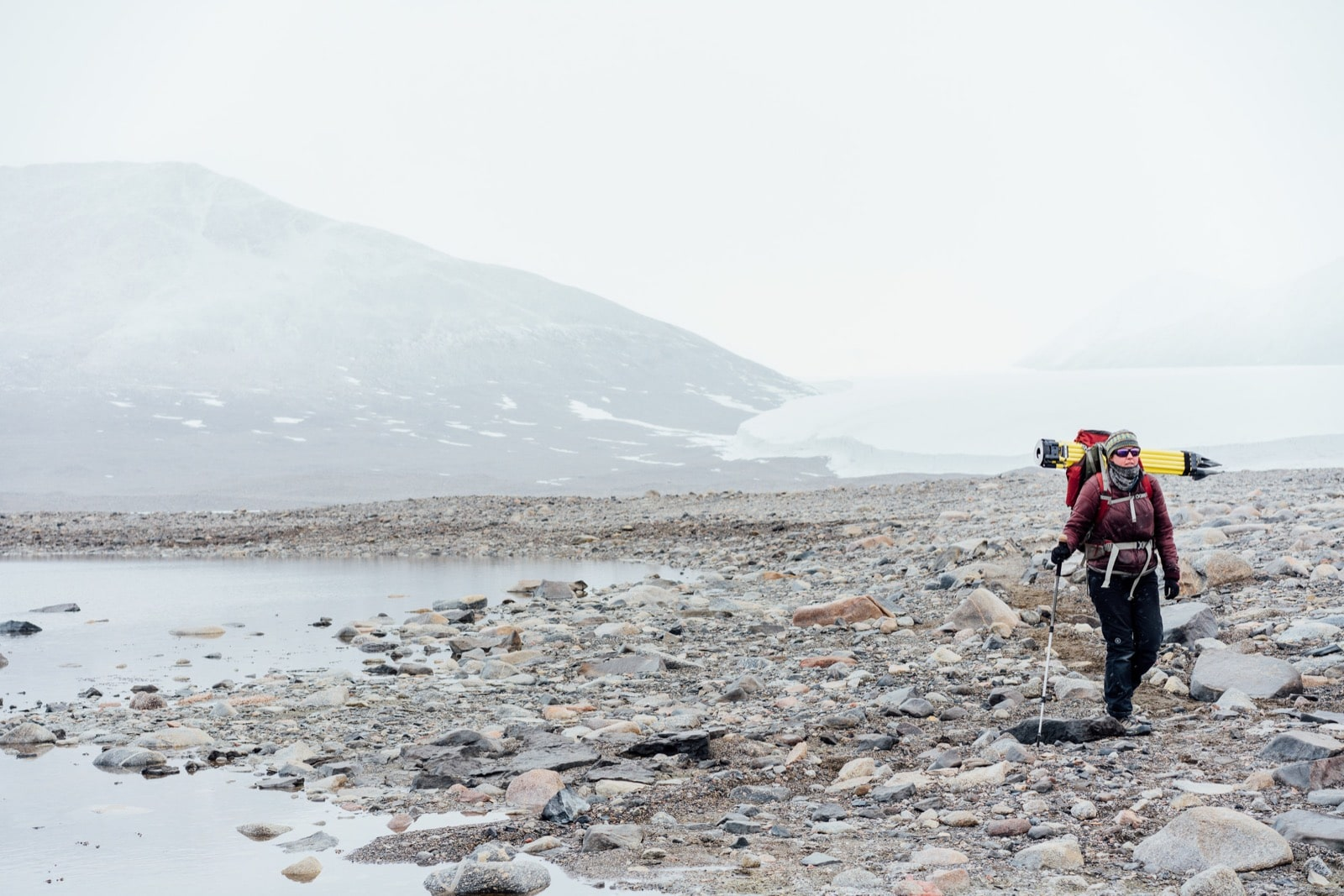 a woman carrying a lot of gear hikes in a rocky barren terrain. to the left is a small bank of water and behind is the edge of a glacier.