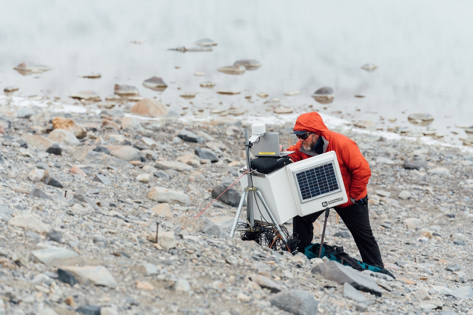 Mike Gooseff with his light red overcoat hood up over his head, working a box of lab equipment. He is standing in front of a bank of water on a rocky shore.