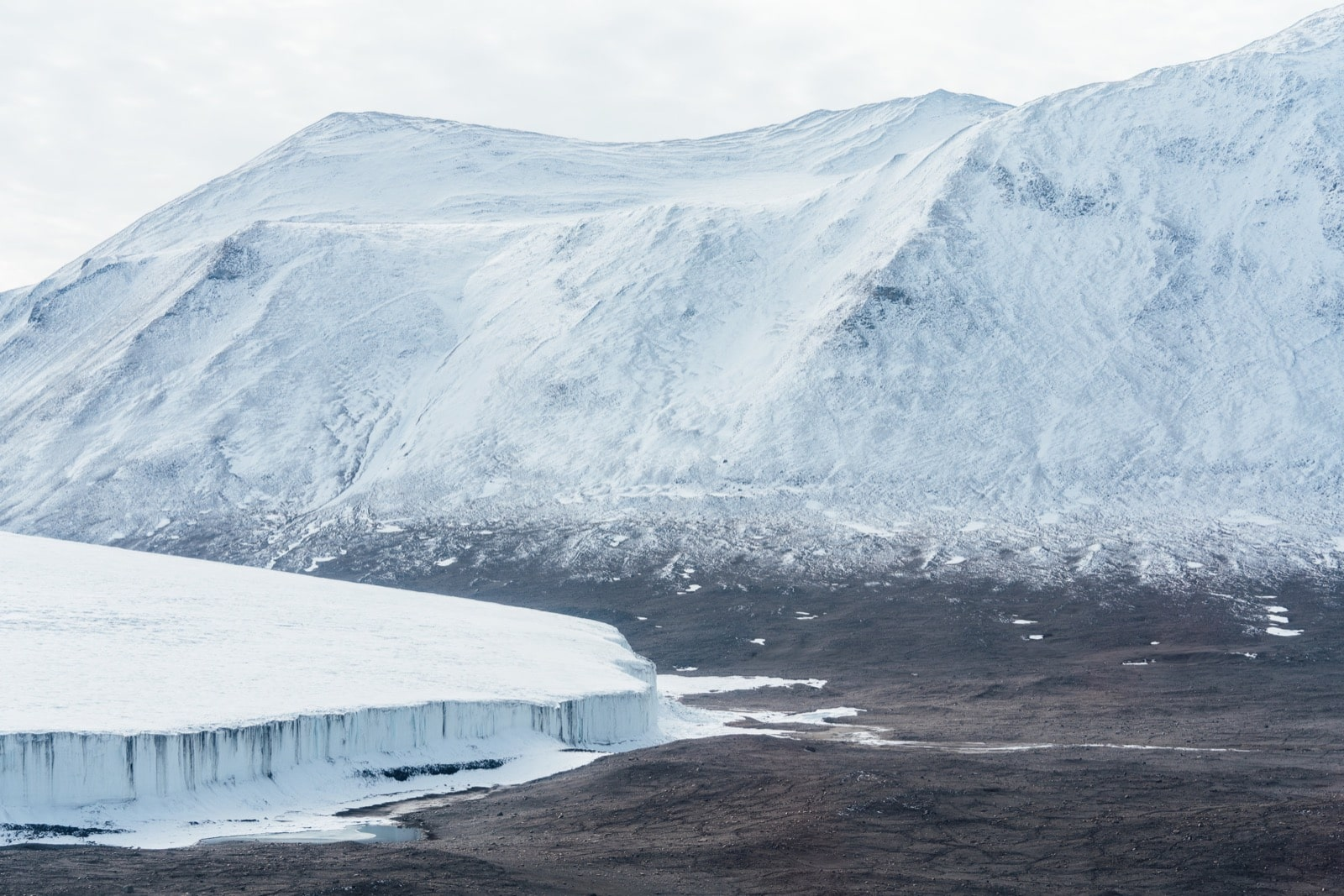 a beautiful landscape shot of white, baby blue capped mountains. below at the base of the mountain is a large glacier