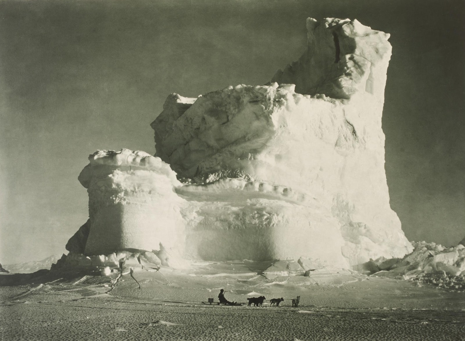 """A party member of the British Antarctic Expedition journeys by dogsled in front of a weathered iceberg, nicknamed """"The Castle Berg."""" Photo by Herbert G. Ponting/ © Victoria and Albert Museum, London"""