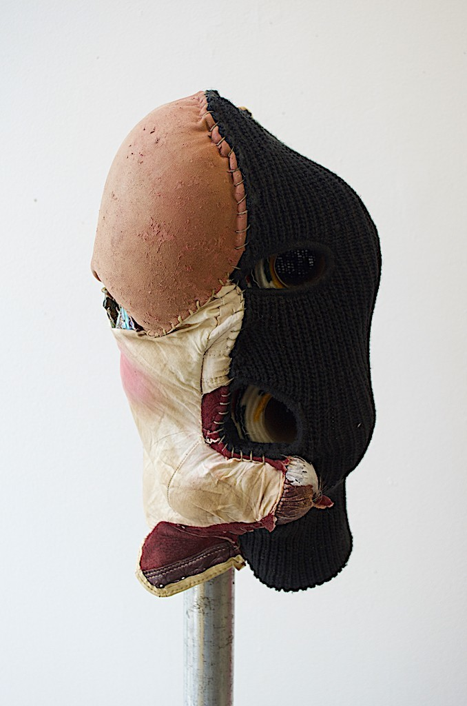 Natalie Ball Pussy Hat 2018 balaclava, leather boxing gloves, Hudson's Bay Co. Trade Blanket toilet paper rolls, sinew thread, blush, human hair, abalone shells, galvanized pipe with floor flange. (head) 14'' x 7.5'' x 5.5''; (galv. pipe) 5' x 1.25'' x 1''; (floor flange) 1.25''  courtesy of the artist.