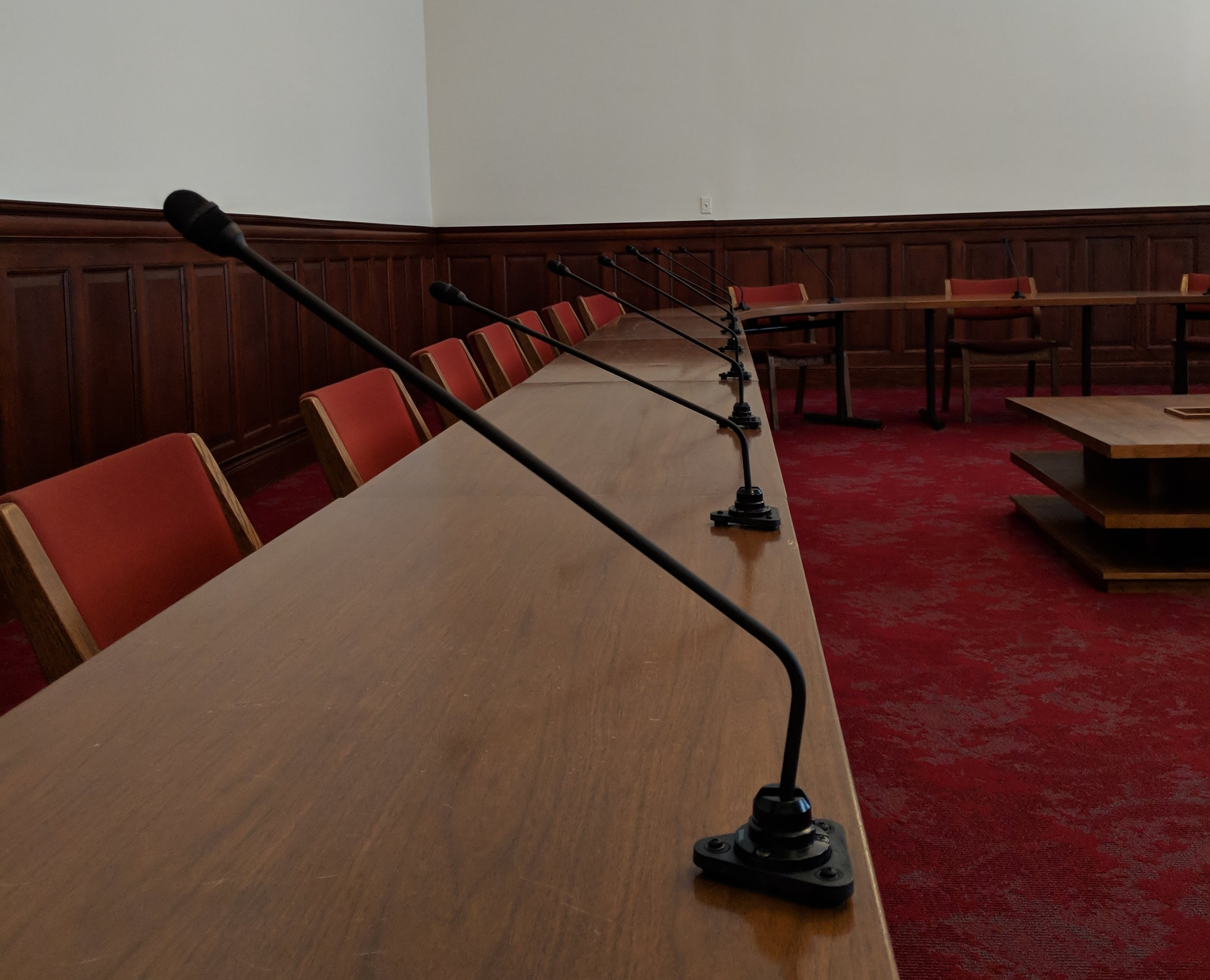 There are a total of 23 microphones on the conference table.