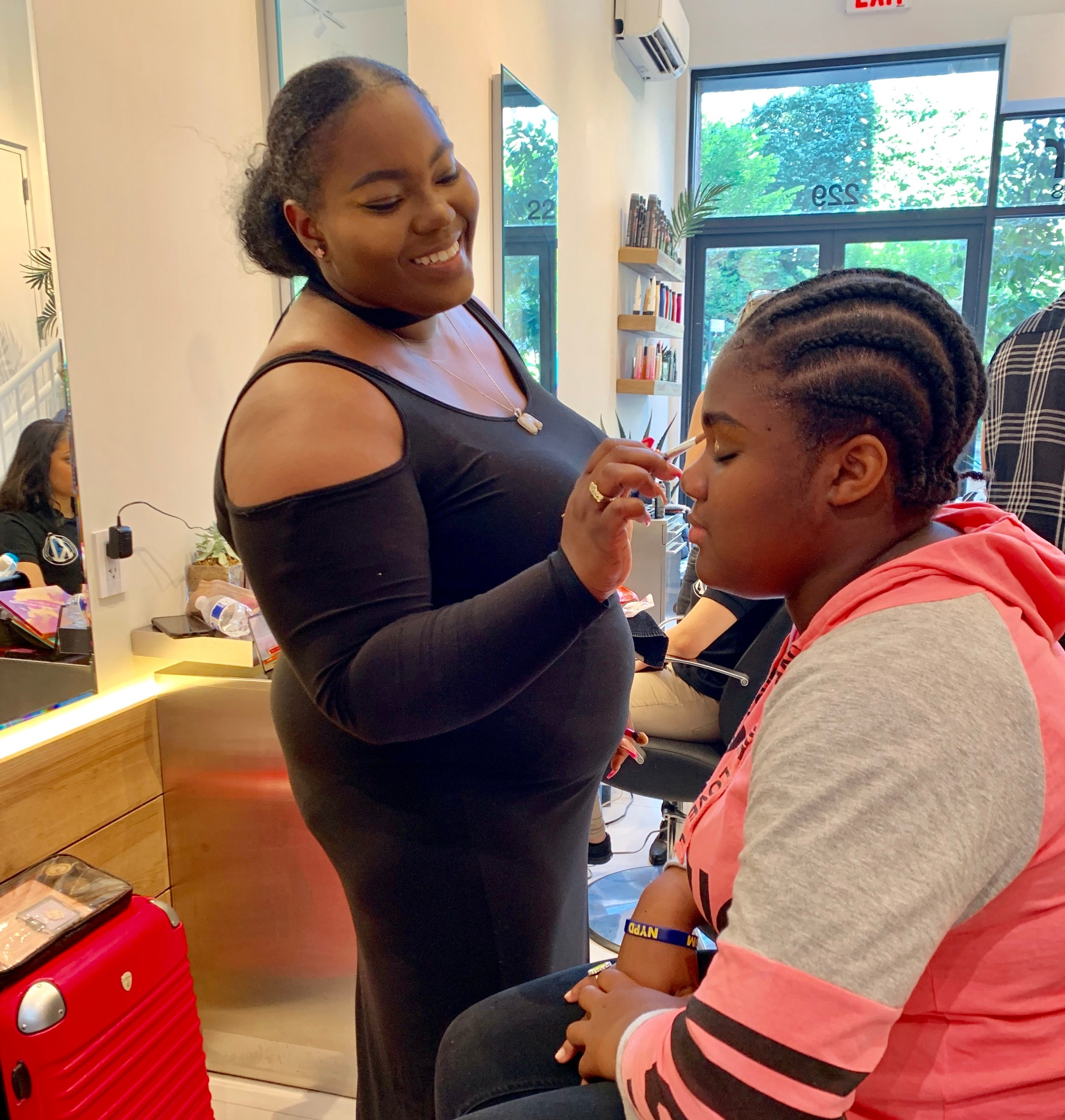 A makeup artist prepares a Day of Empowerment attendee for her first Professional Headshot.