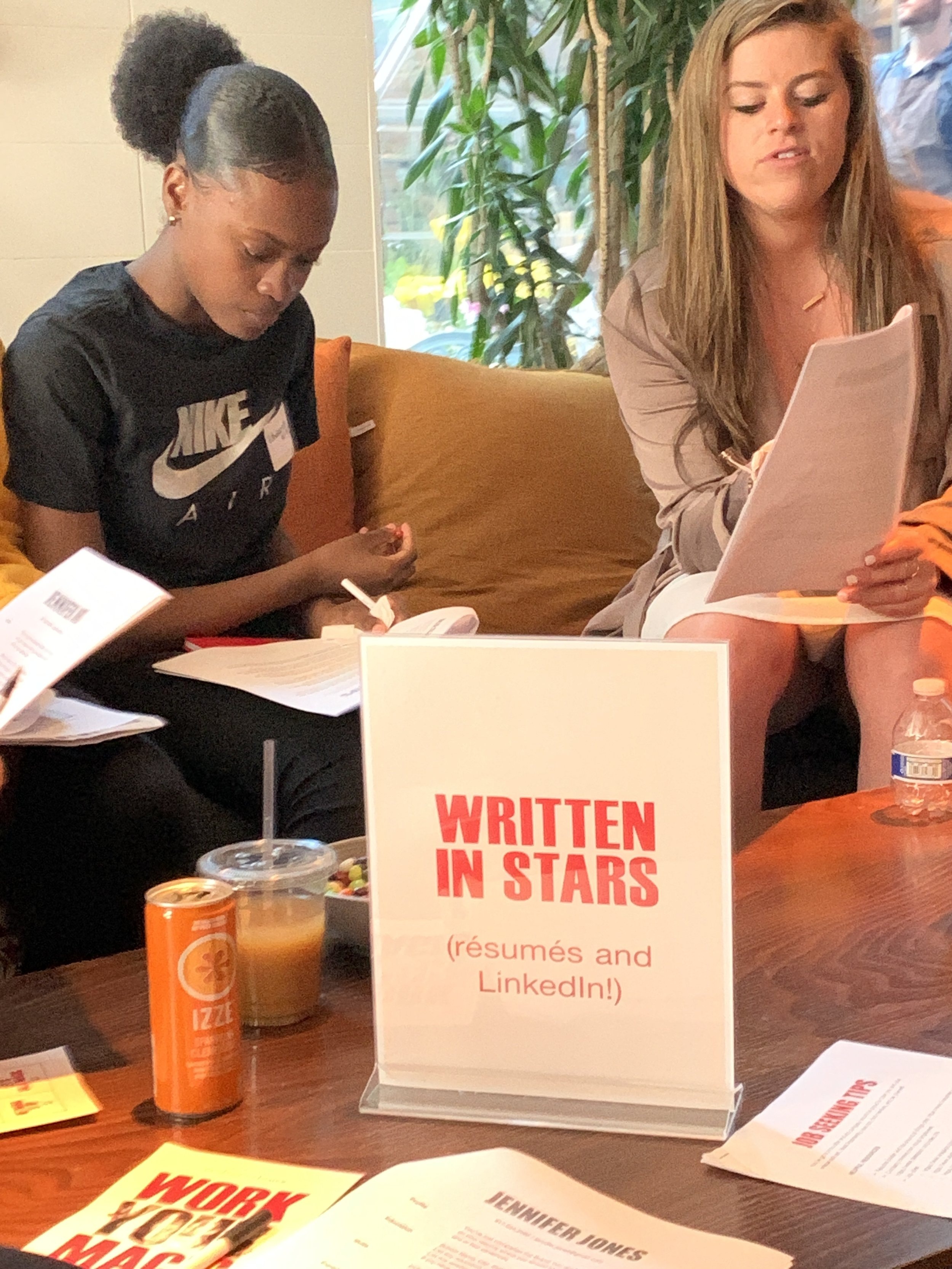 A volunteer from Ellevest runs the Written In Stars resume writing workshop with a group of Day of Empowerment attendees.