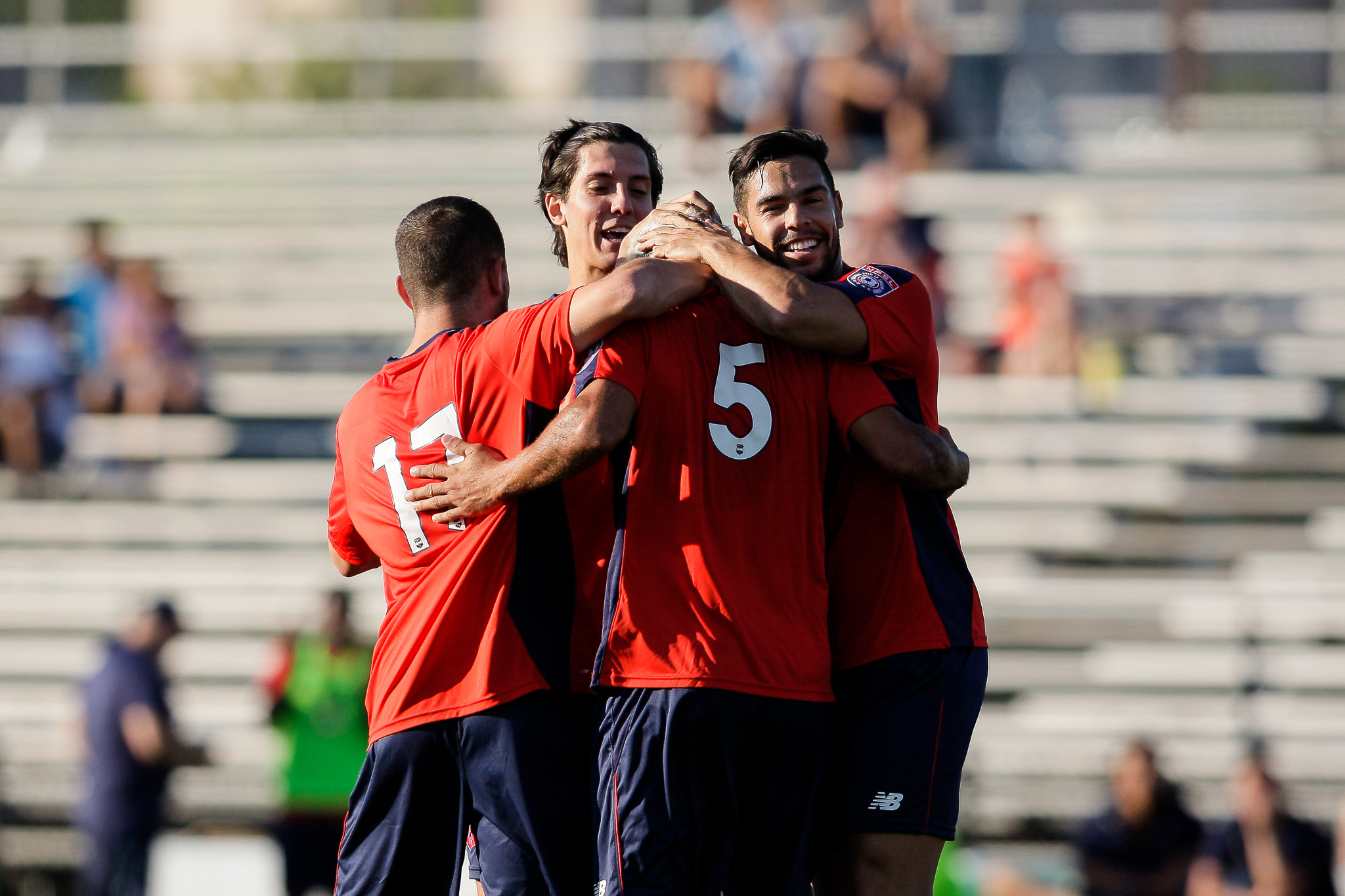 Boston City FC players mob Pedro Silva, #5, after he scores to even the game at 1-1. (c) Burt Granofsky