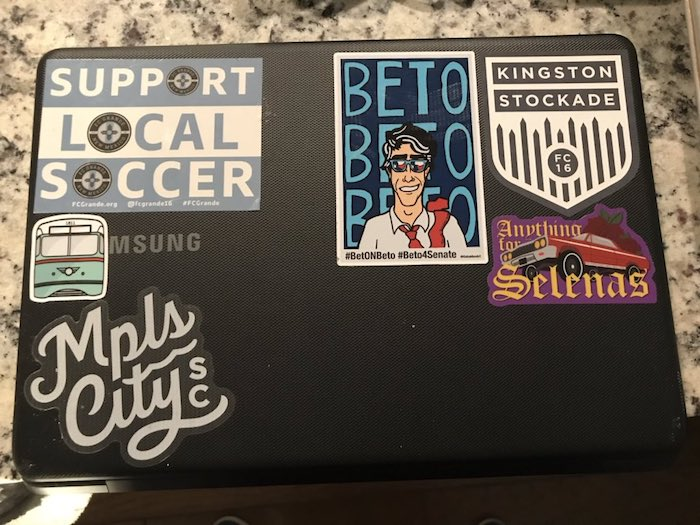 The editor's laptop, featuring several stickers from lower tier clubs.