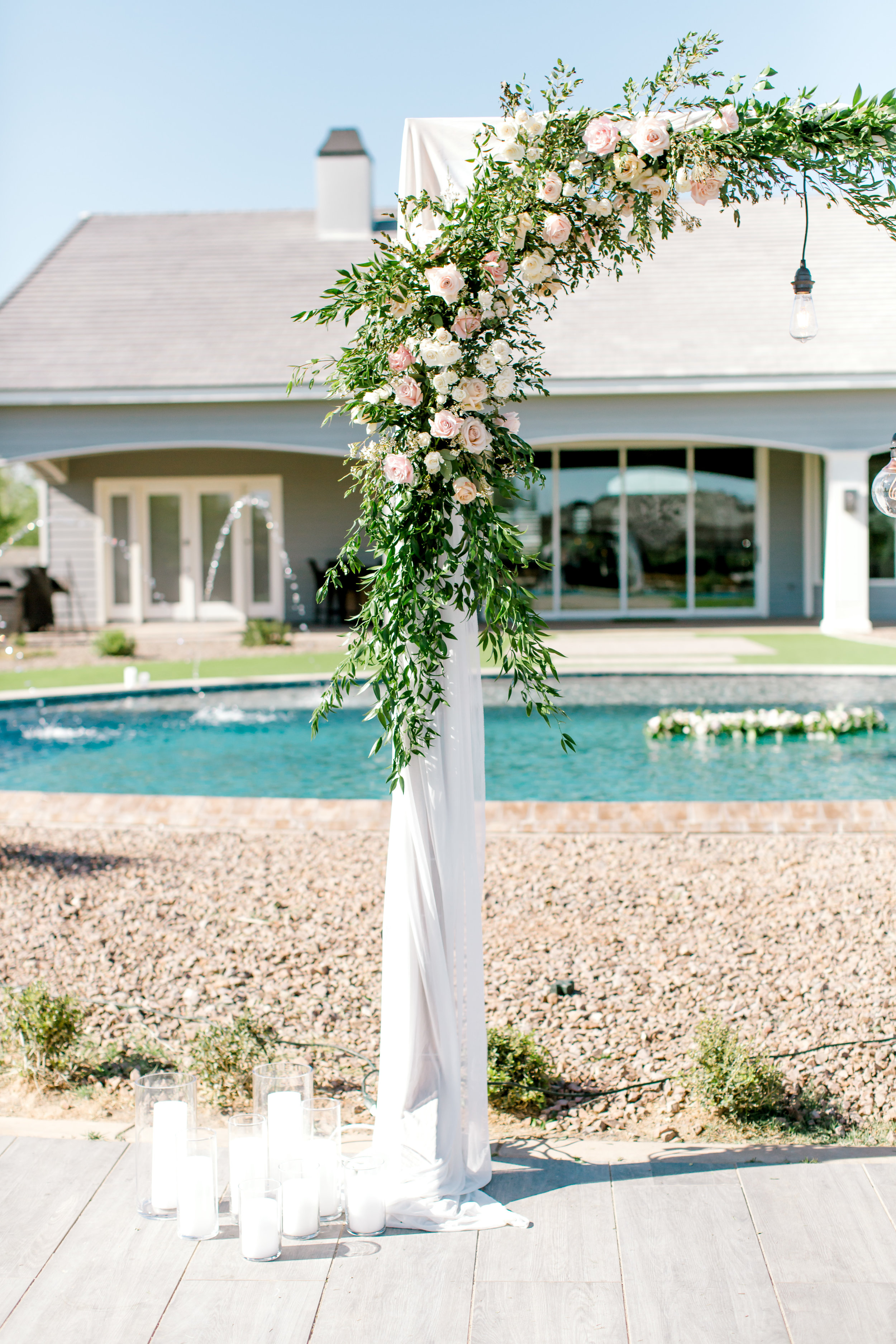 Blush and white backyard wedding - Arch with draping and white candles