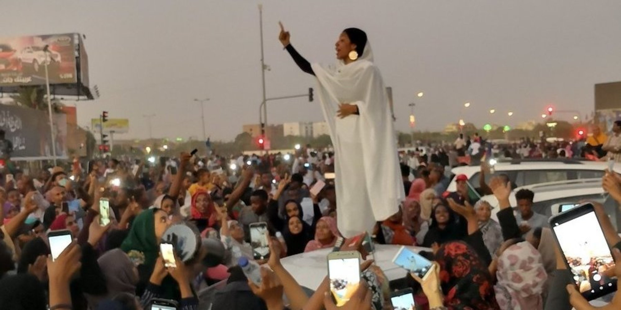 """22-year-old student  Alaa Salah , standing on the roof of a car and leading fellow protestors in chanting """"revolution."""""""