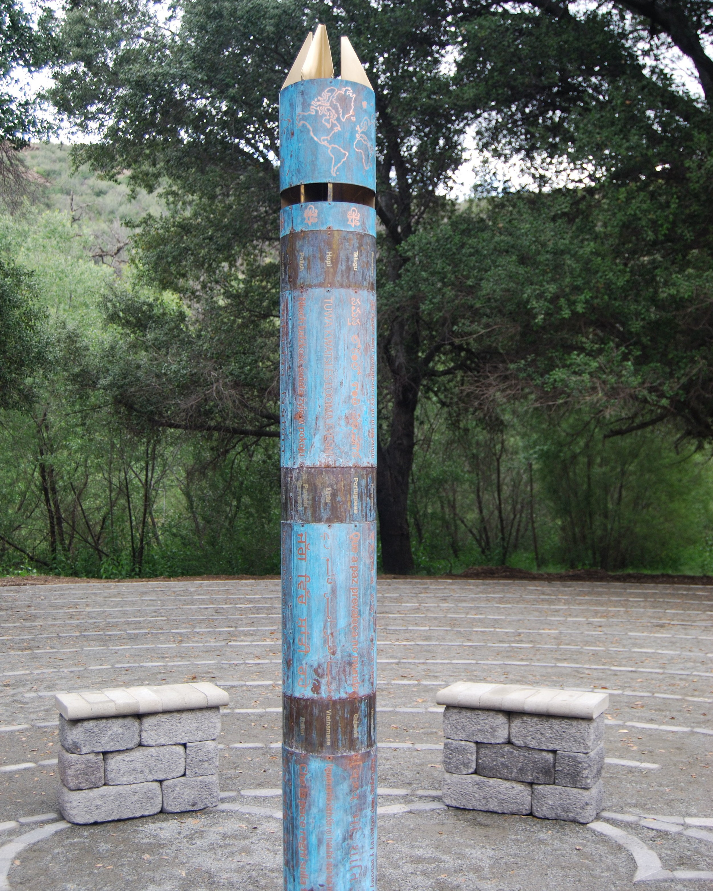 "Peace Pole - Standing tall in the center of the labyrinth, our peace pole is a symbol of hope. Specifically designed by artist Joel Selmeier for The Unity Center, it is made of copper and bronze.The words ""May peace prevail on earth"" are written in 33 different languages including Kumeyaay, the nearly extinct language of the Native Americans who originally occupied this area. Our Unity symbol which features symbols from seven major world religions and an image of the world, encircle the top of the pole.""If prayer ever works, if artistic expression ever has an effect, if there ever is value in building a monument to anything, it seems to me that one ought to be built for peace."" Joel Selmeier, Peace Pole Designer"