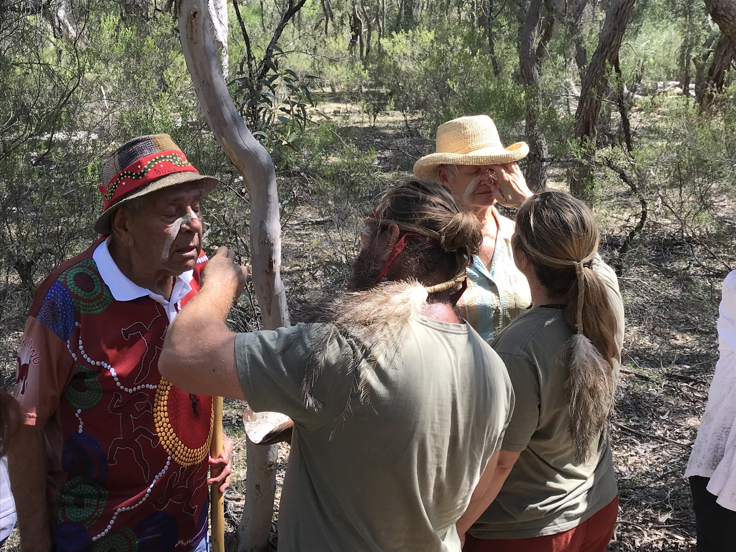 Elders receive ochre (Aboriginal ceremonial face paint) from Milan Dhiiyaan cultural leaders.