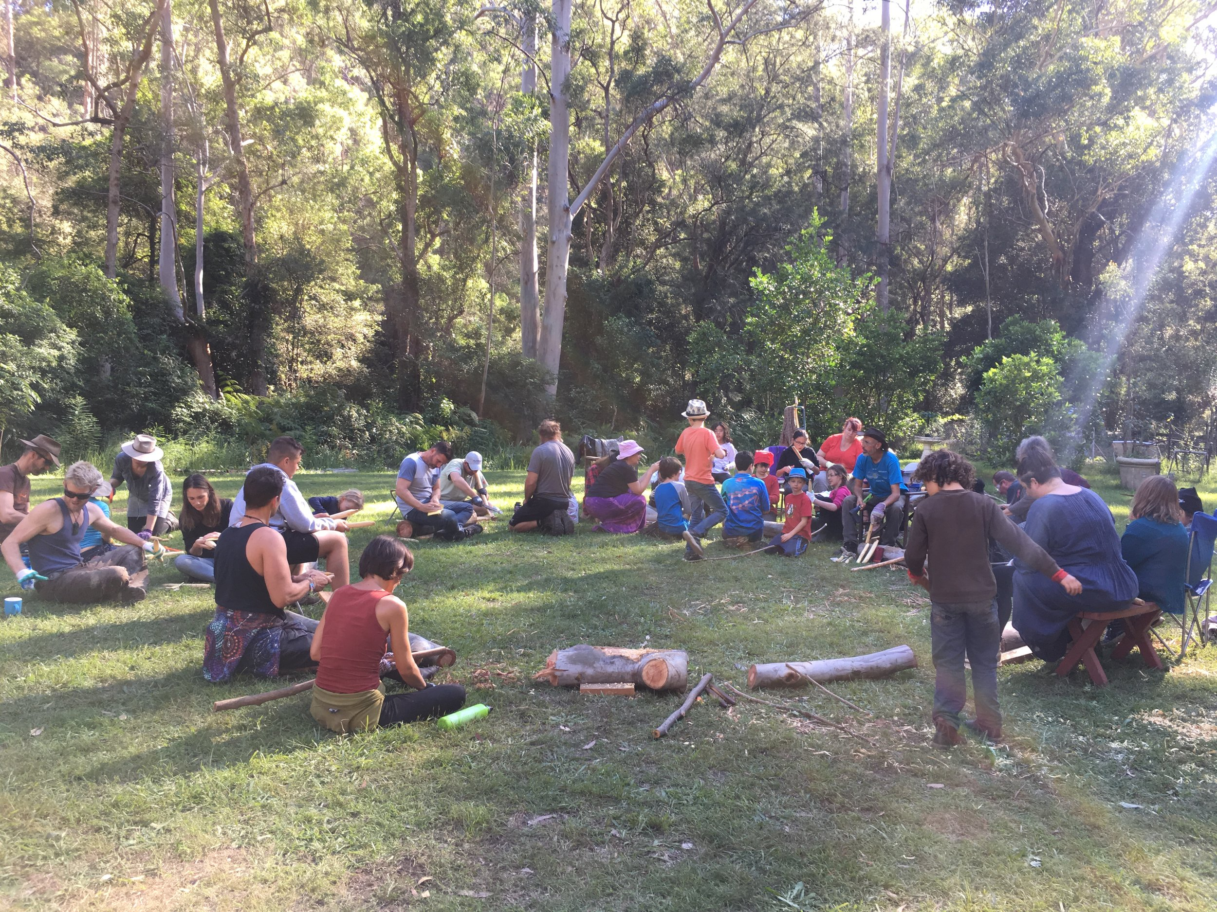 Participants enjoying themselves in the bush at an Aboriginal cultural woodcrafting workshop making clap sticks.