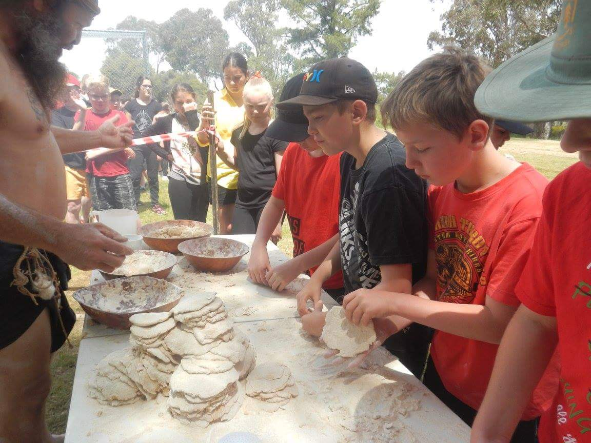 """Students learn how to cook """"Johnny Cakes"""" (Aboriginal bread) on the open fire with Milan Dhiiyaan."""